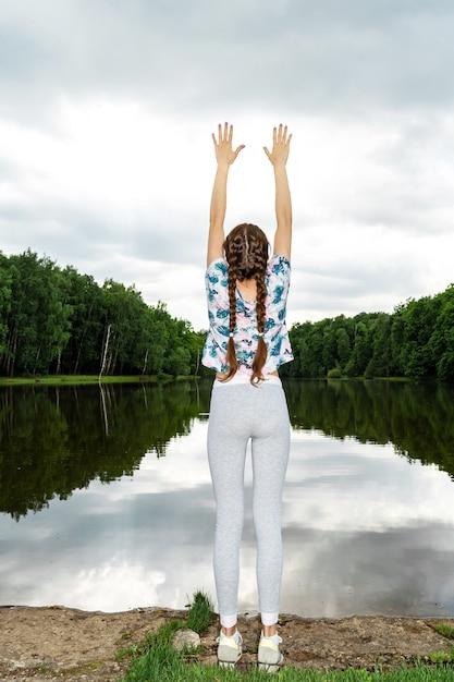 その少女は湖でヨガに取り組んでいます。 Premium写真