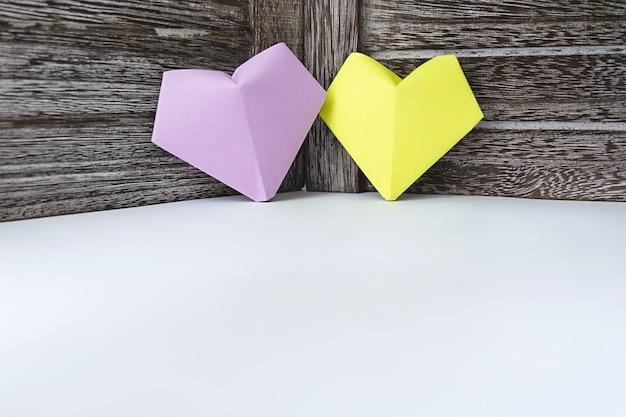 紙のライラックと黄色の色の心は暗い木の板の背景にあります。 Premium写真