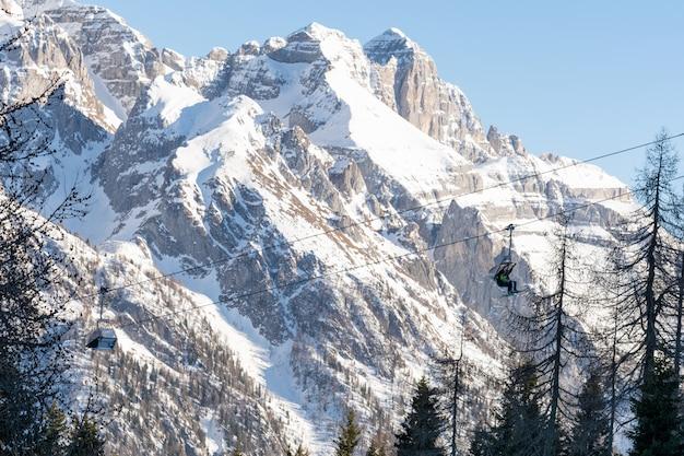 冬。人々は、雪をかぶった山々に囲まれたスキーリフトにチェアリフトを登ります。スキー、風景の概念。 Premium写真