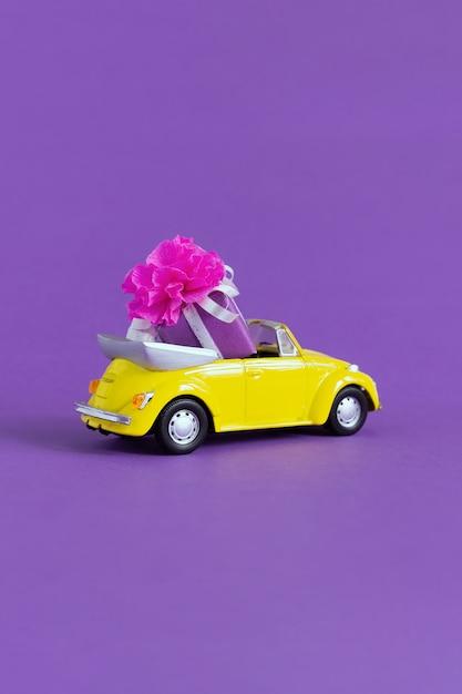 Взгляд малого красочного желтого автомобиля в котором подарочная коробка с смычком на пурпуре. концепция праздника, транспорт, день святого валентина, игрушки Premium Фотографии