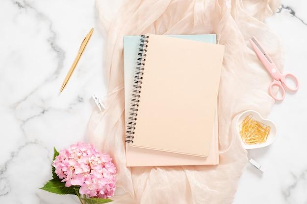ピンクのアジサイの花、パステル毛布、白紙のメモ帳、黄金のひな形、フェミニンなアクセサリーを備えたモダンなホームオフィスデスクワークスペース Premium写真