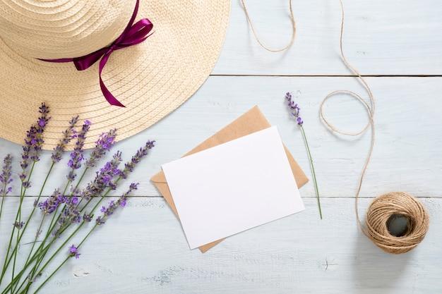 Винтажный конверт, макет пустой бумажной карточки, цветы лаванды, соломенная шляпа и шпагат Premium Фотографии