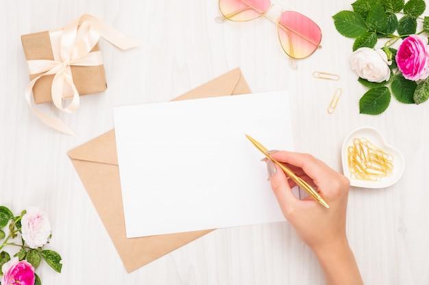結婚式の招待カードやラブレターを書くトップビュー女性手。 Premium写真