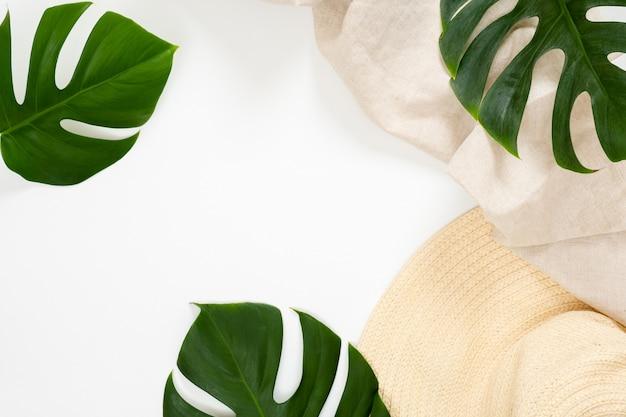 Концепция летних каникул с тропическими листьями монстера и соломенной шляпе на белом фоне Premium Фотографии