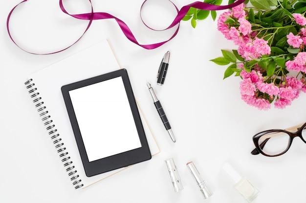 Современное рабочее место для домашнего офиса с планшетом для электронных книг, женскими аксессуарами, очками, бумажным блокнотом, букетом розовых роз Premium Фотографии