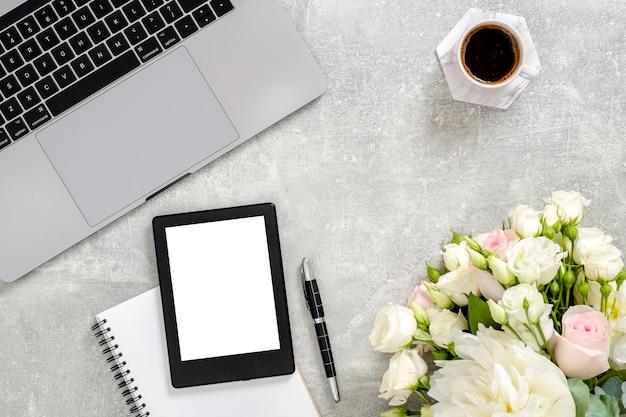 Женский портативный компьютер рабочей области, пустой экземпляр космический макет экран планшета, чашка кофе, дневник, цветы на бетонном камне. Premium Фотографии