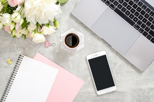Стильный бетонный камень офисный рабочий стол с ноутбуком, чашкой кофе, цветами, женская рука, написание текста в бумажном блокноте, блокнот Premium Фотографии