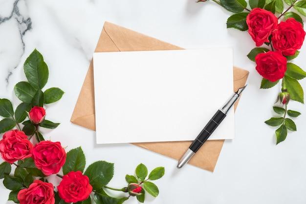 Открытка-макет с бумажным конвертом, ручкой и рамкой из розовых цветов Premium Фотографии
