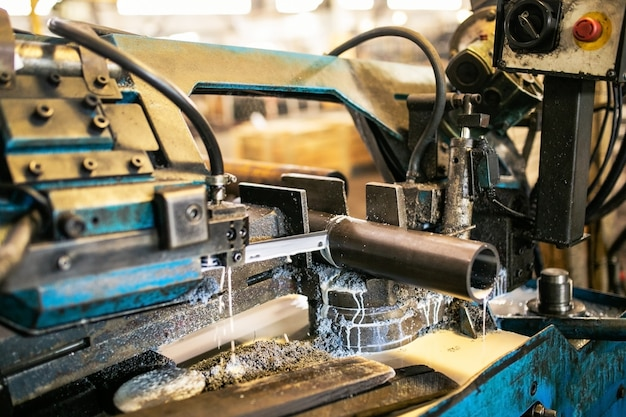 バンドソーの切断機は、原料金属を冷却液でロッドにします。 Premium写真