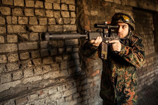 Солдат на войне целится с оружием Premium Фотографии