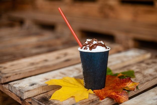 秋、紅葉、木製テーブルの上のコーヒーの熱い蒸しカップ Premium写真
