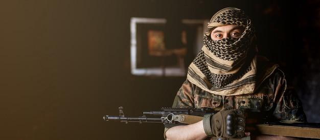 Арабский солдат в головном уборе из национальной куфии с оружием в руках Premium Фотографии