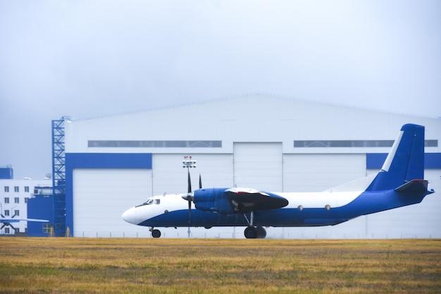 Бизнес-самолет покидает авиационный бокс на взлетно-посадочной полосе аэропорта в пасмурную погоду с дождем Premium Фотографии