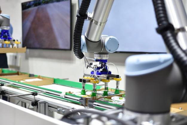 人工知能を備えた機械式ロボットがコンベア上で製品を分類する Premium写真