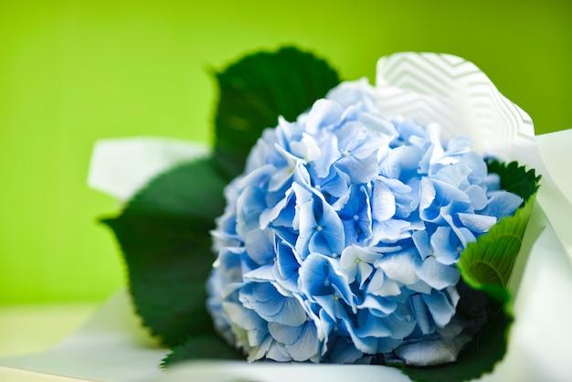 緑の背景に青い花の花束 Premium写真