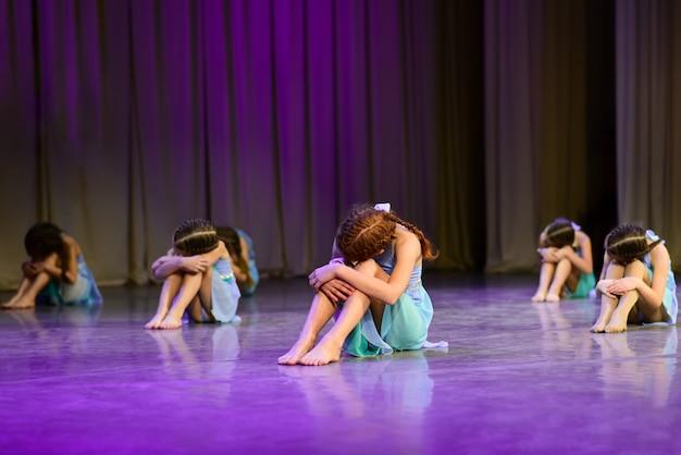 ダンサーの女の子が舞台に座る、ドラマチックなダンス Premium写真