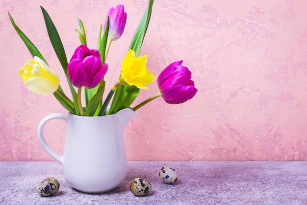 白い花瓶のチューリップと水仙の春の花束。イースターのグリーティングカード Premium写真