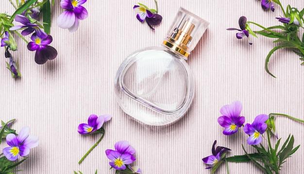 Женская бутылка духов и фиалки цветы на розовом фоне Premium Фотографии