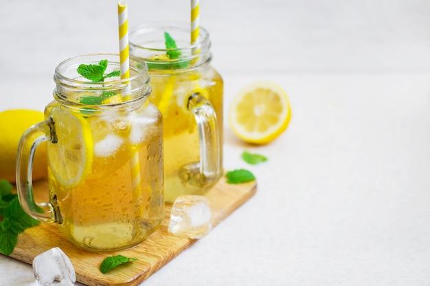 ガラスの瓶にレモンとミントのグリーンアイスティー。 Premium写真