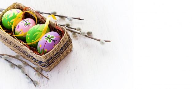 塗装卵と猫柳のイースターの背景。 Premium写真