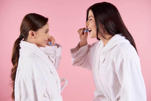 Мать и дочь в халатах чистит зубы. Premium Фотографии