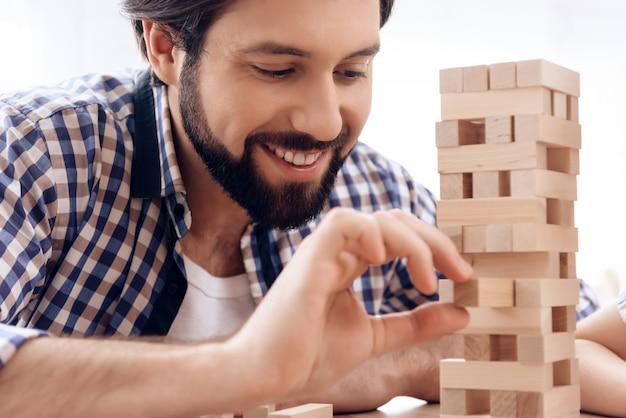 ひげを生やした男の笑みを浮かべて塔から木のブロックを削除します。 Premium写真
