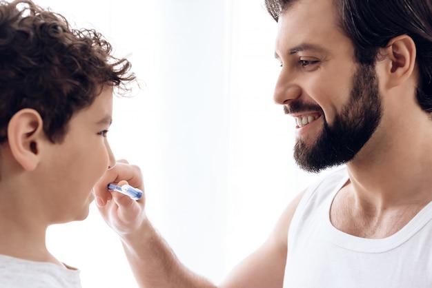 幸せな父は、若い息子の歯を歯ブラシで磨きます。 Premium写真