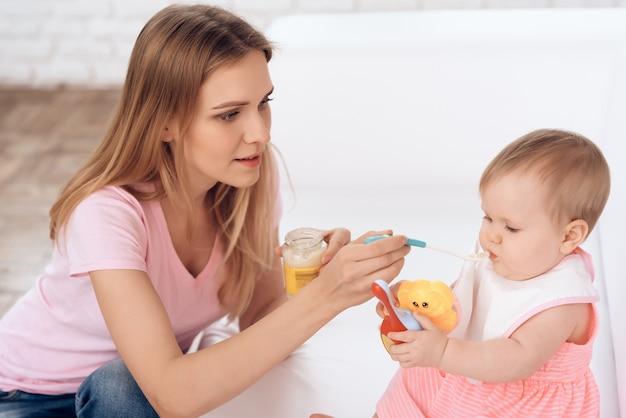 Мать с пюре кормления новорожденного в домашних условиях. Premium Фотографии