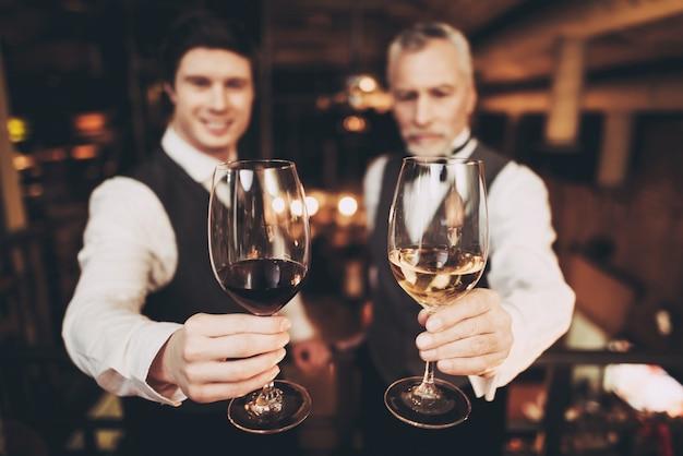 ソムリエは赤と白ワインのグラスを持っています。 Premium写真
