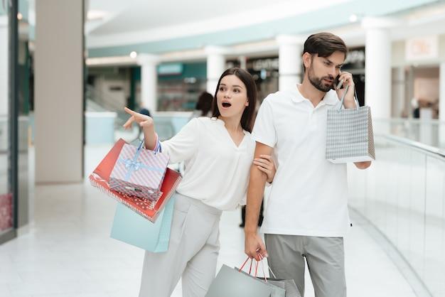 女性は店に行きたいのですが、男性は電話で話しているのに忙しいです。 Premium写真