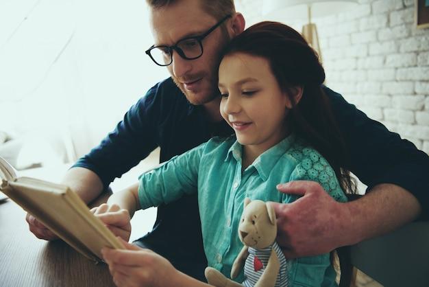 Рыжий отец в очках читает книгу. Premium Фотографии