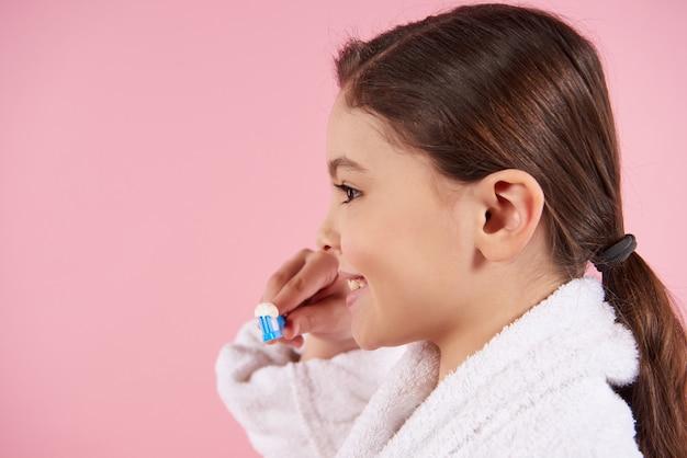 バスローブの少女は歯を磨いています。 Premium写真
