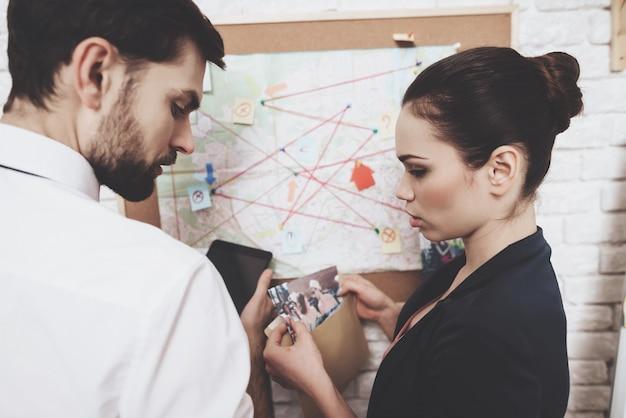 ネクタイの男とジャケットの女性は地図を見ています。 Premium写真