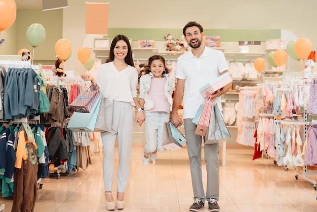 Люди в магазине одежды тк. девочка прыгает. Premium Фотографии