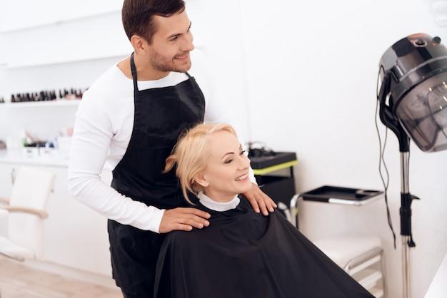 女性は美容院で髪型をしています。 Premium写真