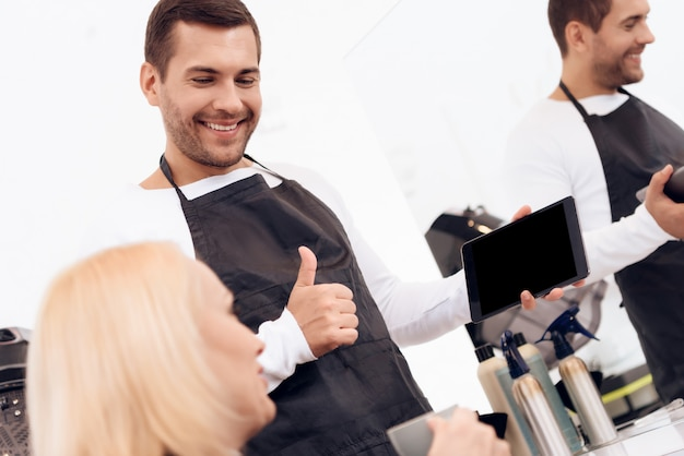 美容師は、タブレット上の女性の散髪を選択します。 Premium写真