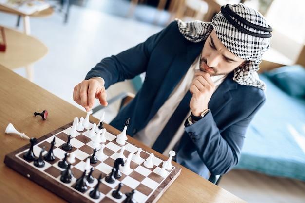 ホテルの部屋でテーブルでチェスをしているアラブのビジネスマン。 Premium写真