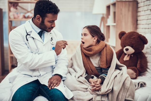 医者は風邪を持つ少女の喉を調べています。 Premium写真