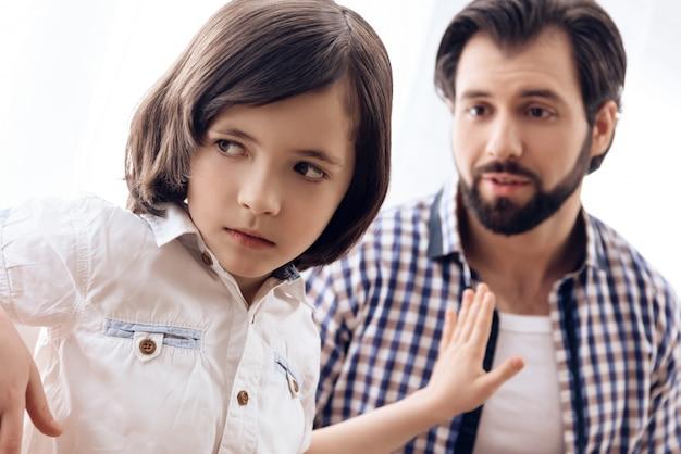 息子はパパを許したくないので、彼を押しのけます。 Premium写真