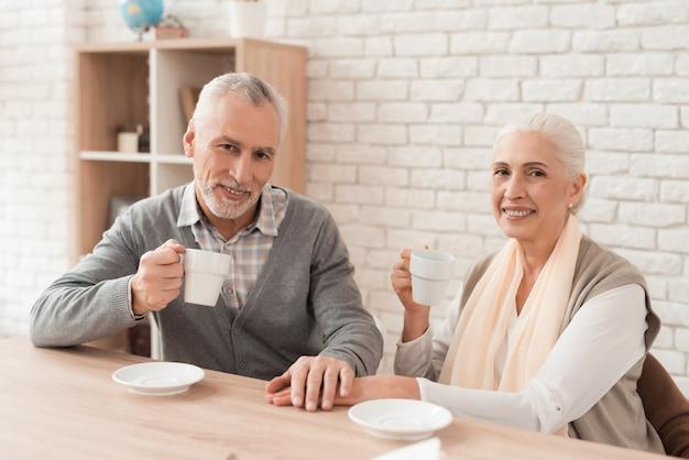 コーヒーを飲みながら、家で一緒に手を繋いでいるカップル。 Premium写真
