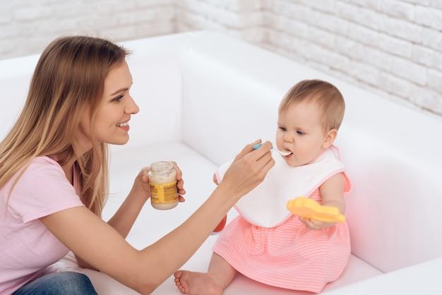 Мать с пюре и ложкой кормления малыша. Premium Фотографии