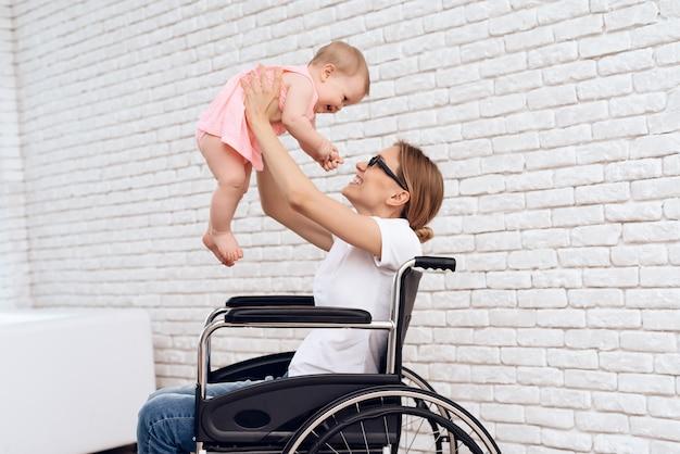 車椅子の母は生まれたばかりの赤ちゃんと遊ぶ。 Premium写真