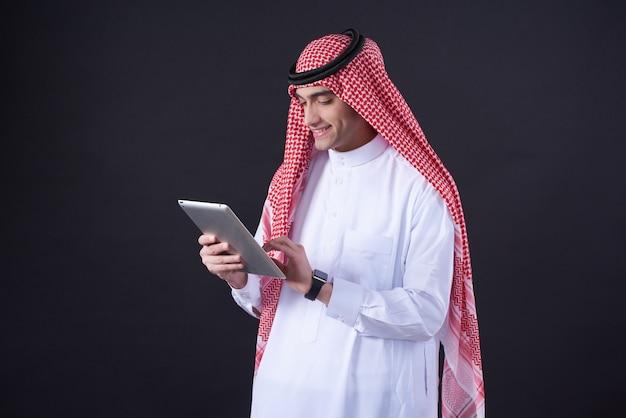 中東の男が分離されたタブレットを使用してポーズします。 Premium写真