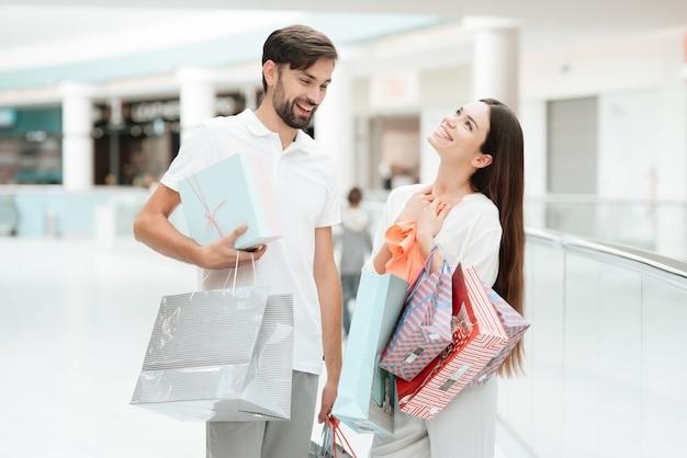 買い物袋を持つ男女が歩いています。 Premium写真