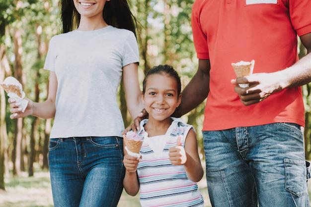 森でアイスクリームを食べる彼女の両親と小さな女の子。 Premium写真