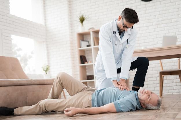 医師は心臓発作のある老人に心肺蘇生をします。 Premium写真
