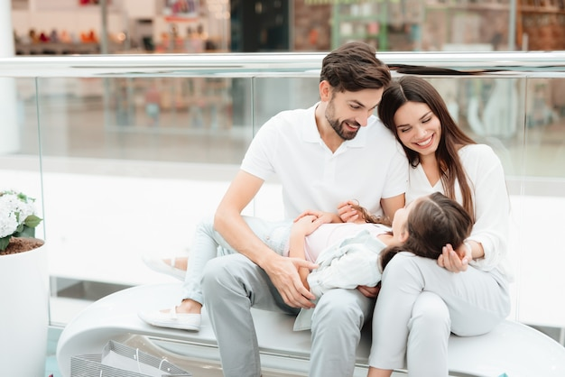 家族はショッピングモールのベンチに座っています。 Premium写真
