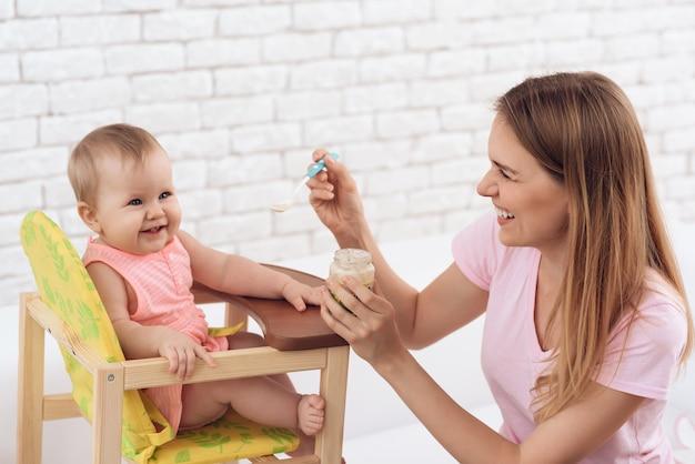 Улыбающаяся мама с пюре, кормящая улыбающегося ребенка Premium Фотографии