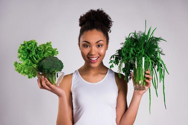 分離された緑を保持しているアフリカ系アメリカ人の女の子。 Premium写真
