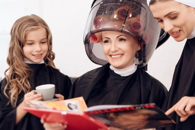 ヘアカーラーを持つ女性は娘と一緒に髪を乾燥させます。 Premium写真